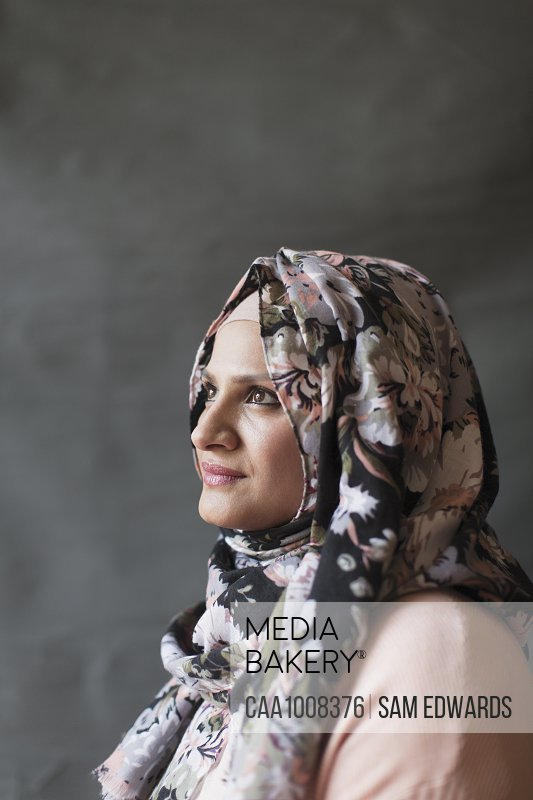 Serene, thoughtful woman in floral hijab looking up