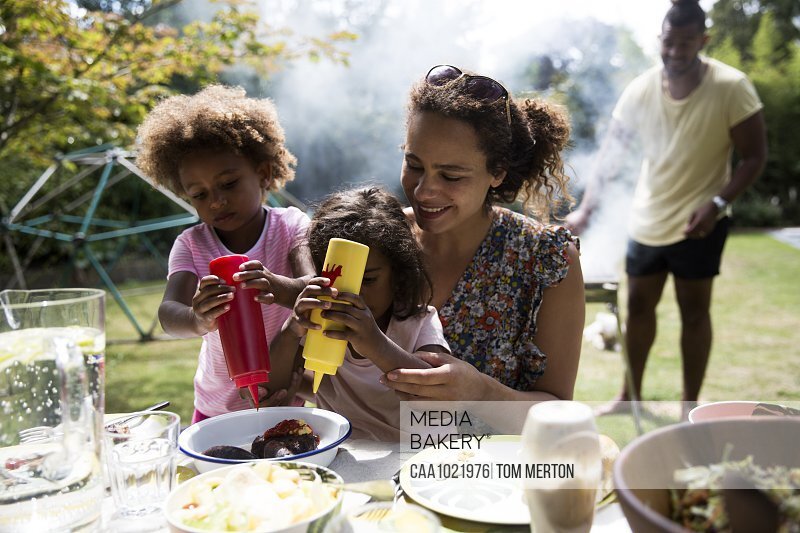 Mother and daughters enjoying barbecue lunch at backyard table