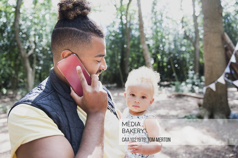 Father holding toddler daughter and talking on smart phone in woods