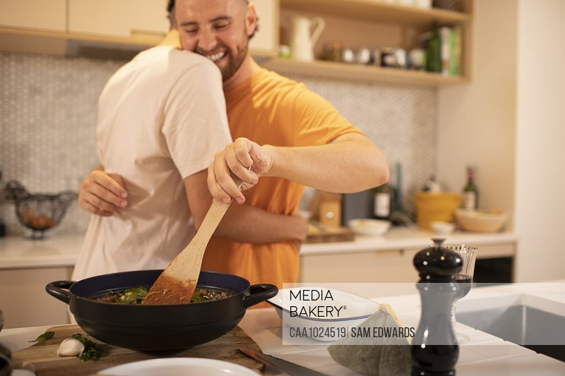Happy gay male couple hugging and cooking in kitchen