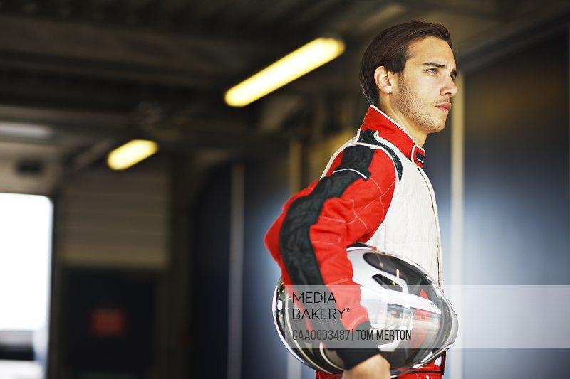 Racer holding helmet in garage