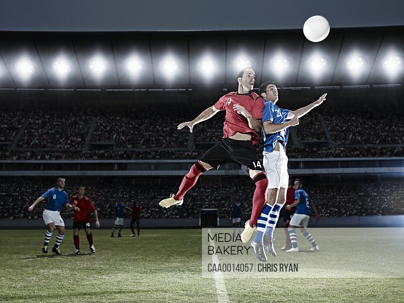 Soccer players jumping for ball on field