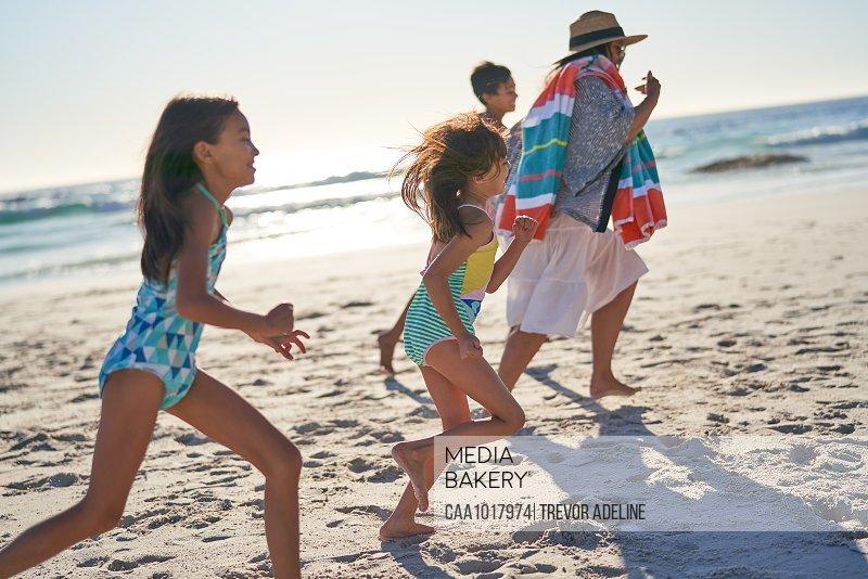 Playful family running on sunny ocean beach