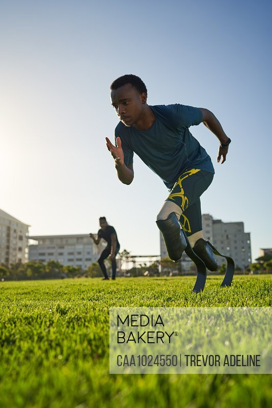 Focused male amputee sprinter training in sunny sports field