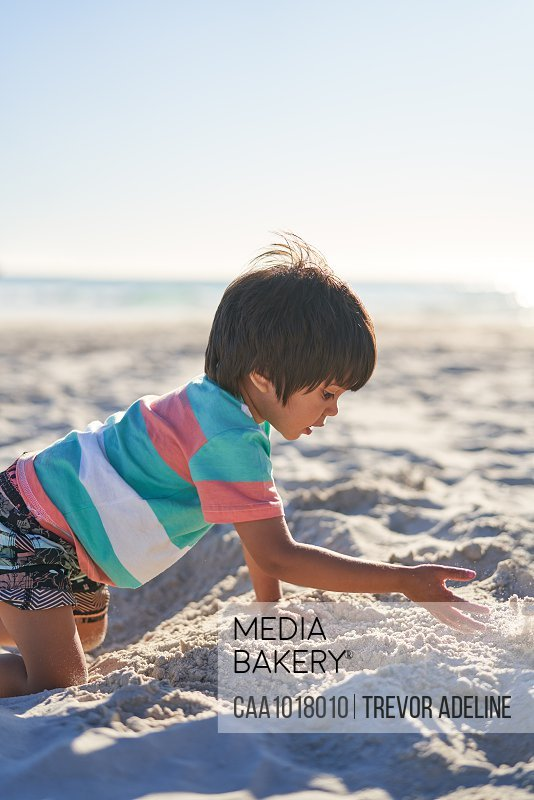 Boy playing in sand on sunny summer beach