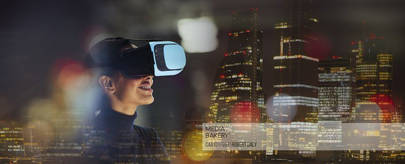 Smiling businesswoman using virtual reality glasses in city at night