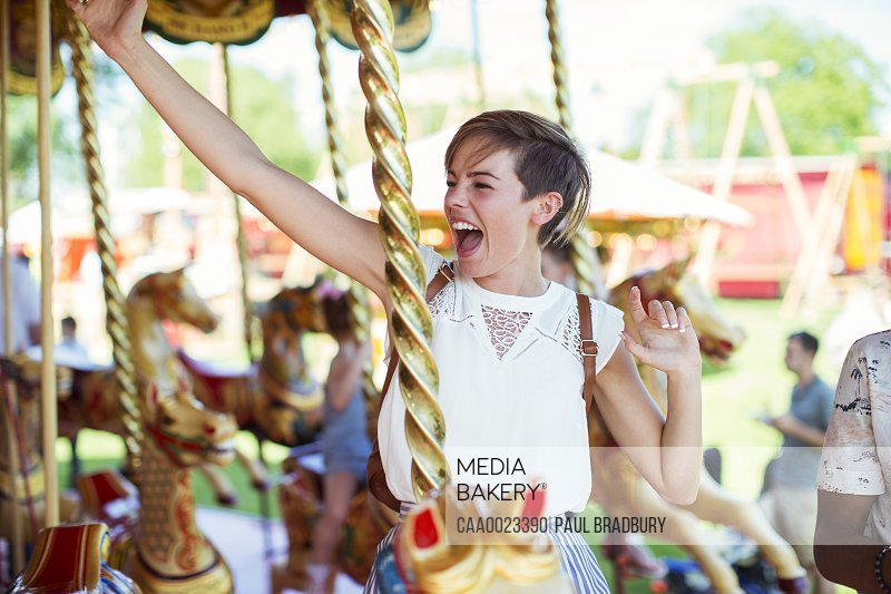 Cheerful woman sitting on horse on carousel in amusement park