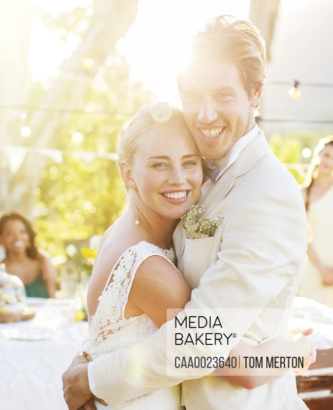 Portrait of young couple embracing in garden during wedding reception