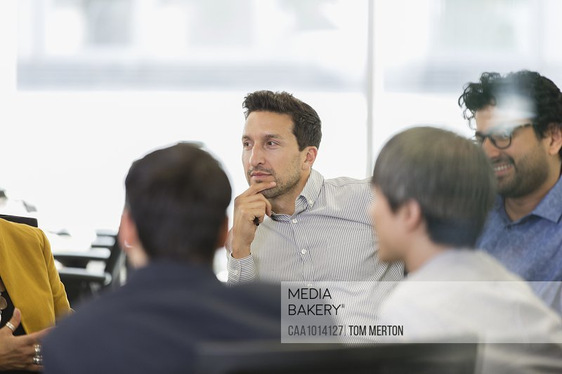 Focused businessman listening in conference room meeting