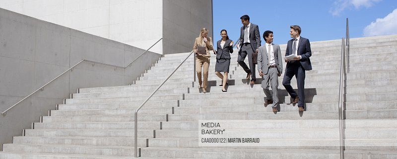 Business people talking and descending urban stairs