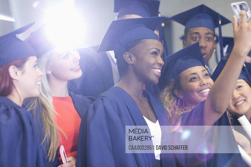 University students taking selfie in corridor after graduation ceremony