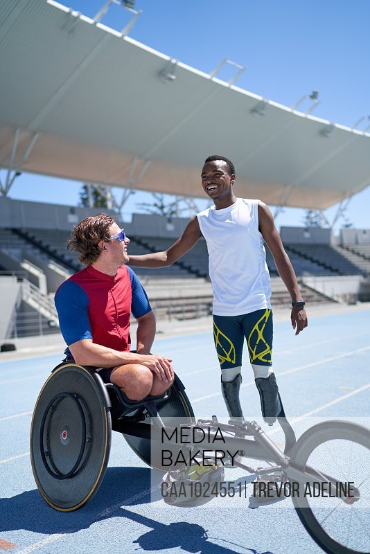 Happy male amputee and paraplegic athlete on sunny sports track