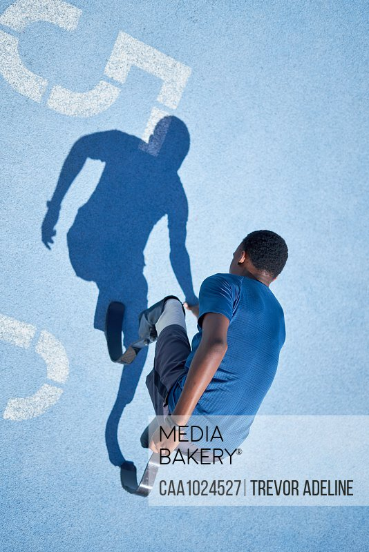 Male amputee sprinter on blue sports track