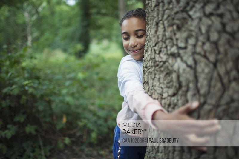 Cute girl hugging tree trunk in woods