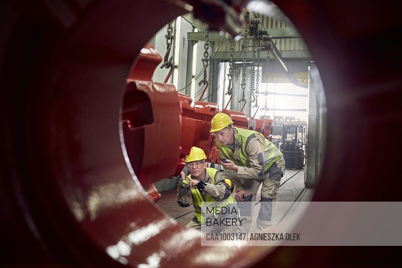 Steelworkers examining steel equipment in steel mill