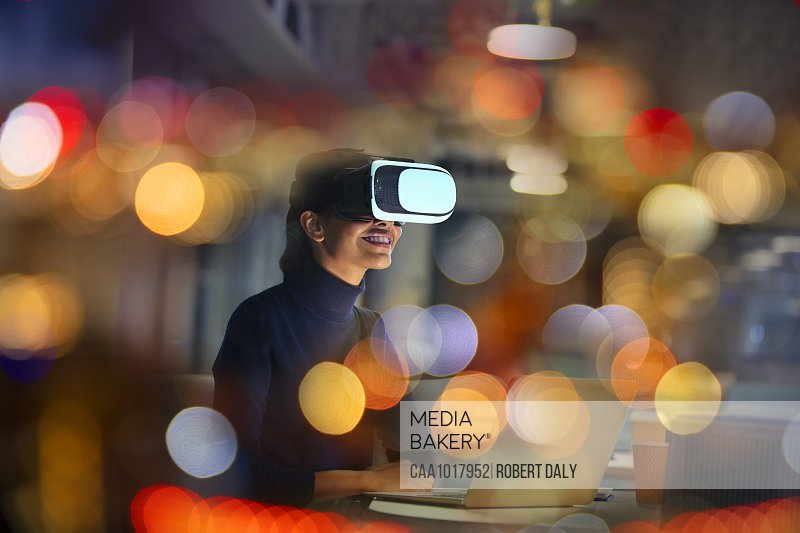 Smiling businesswoman using virtual reality glasses