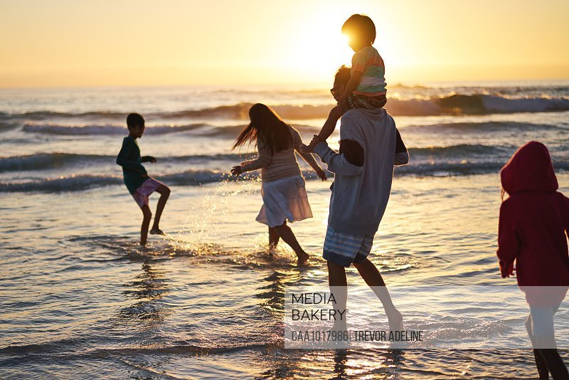 Family playing and splashing in ocean surf at sunset