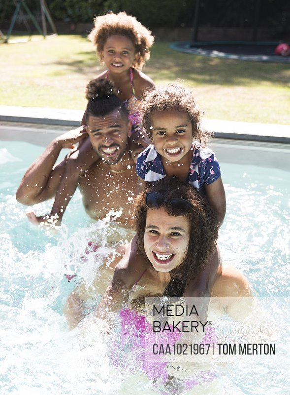Portrait happy family splashing in sunny summer swimming pool