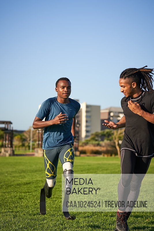 Trainer timing male amputee athlete running in sunny grass