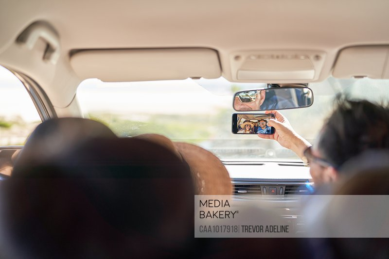 Family taking selfie with camera phone inside car