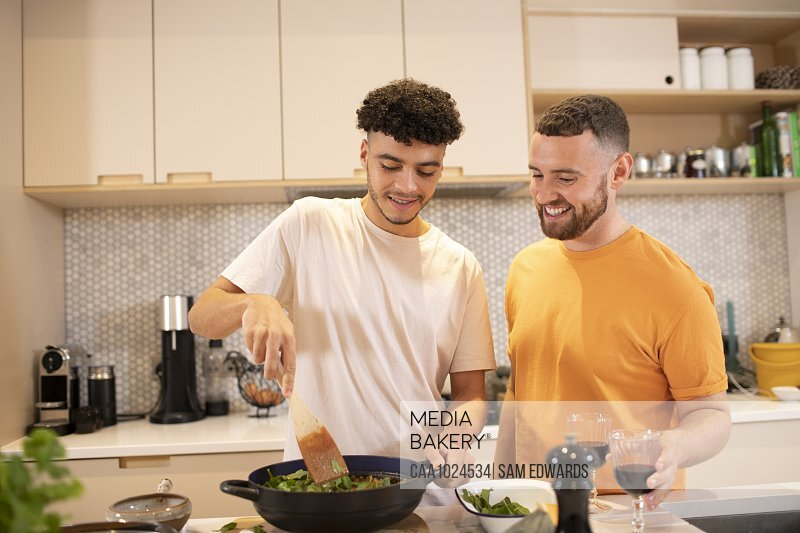 Gay male couple cooking in kitchen