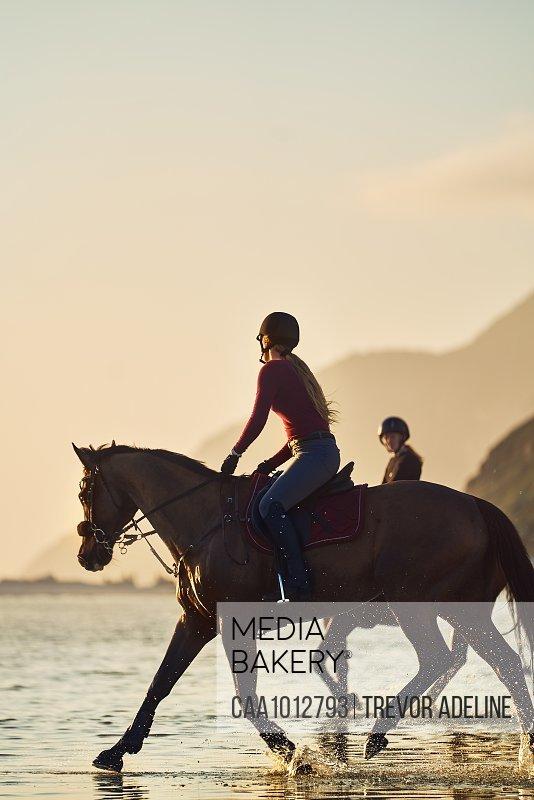 Young woman horseback riding on ocean beach at sunset