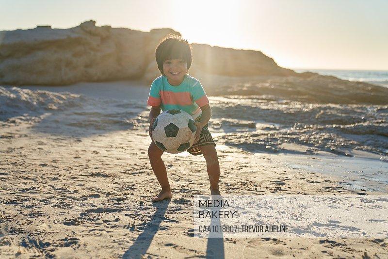 Portrait cute boy playing with soccer ball on sunny beach