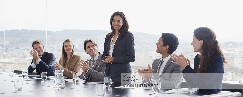 Co-workers clapping for businesswoman in conference room