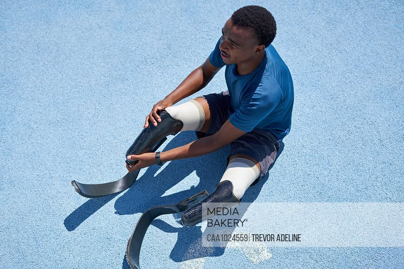 Male amputee sprinter preparing on blue sports track