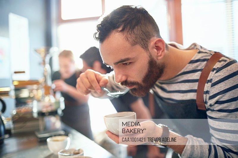 Male coffee roaster tasting coffee