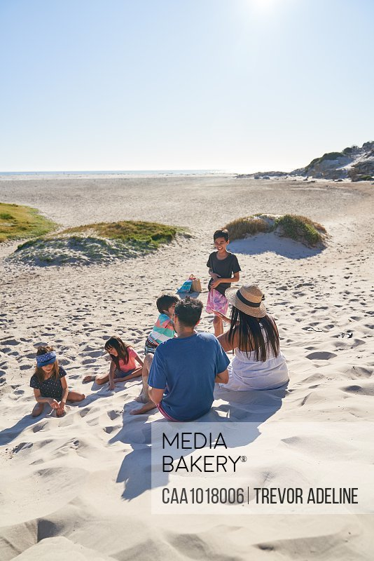 Family playing and relaxing on sunny beach, Cape Town, South Africa