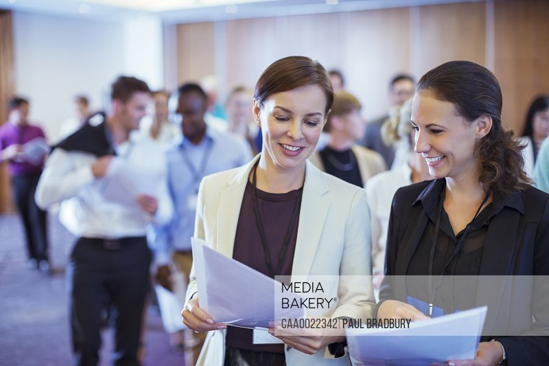 Two young businesswoman looking through files in conference room