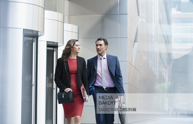 Corporate businessman and businesswoman walking and talking outside building
