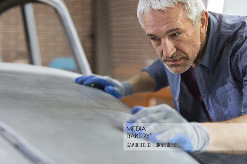Focused mechanic examining automobile hood panel in auto repair shop