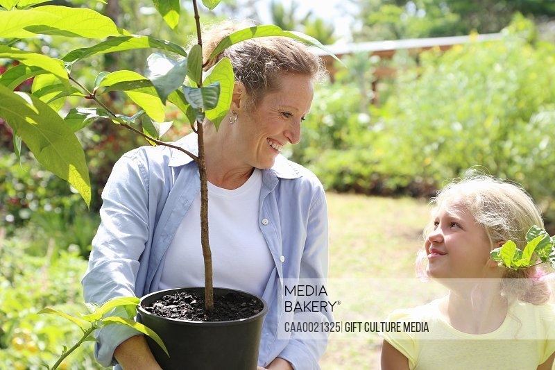 Woman and girl with tree seedling in sunny garden