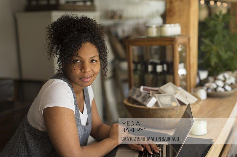Portrait confident female shop owner using laptop in plant nursery