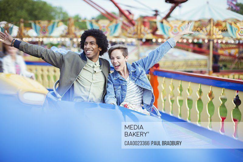 Cheerful couple on carousel in amusement park