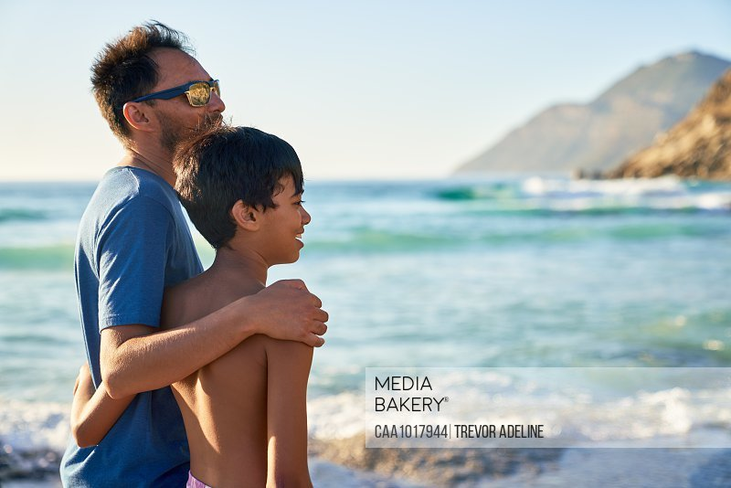 Affectionate father and son hugging on sunny ocean beach