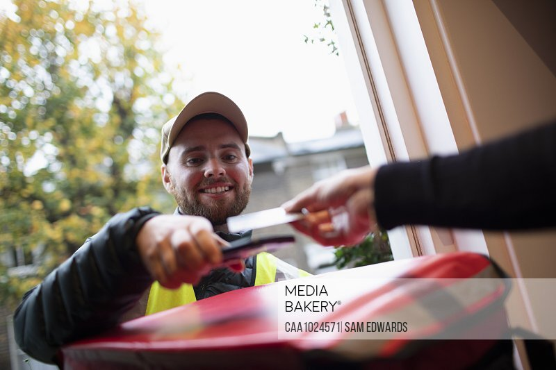 Man paying delivery man for food delivery with smart card at front door