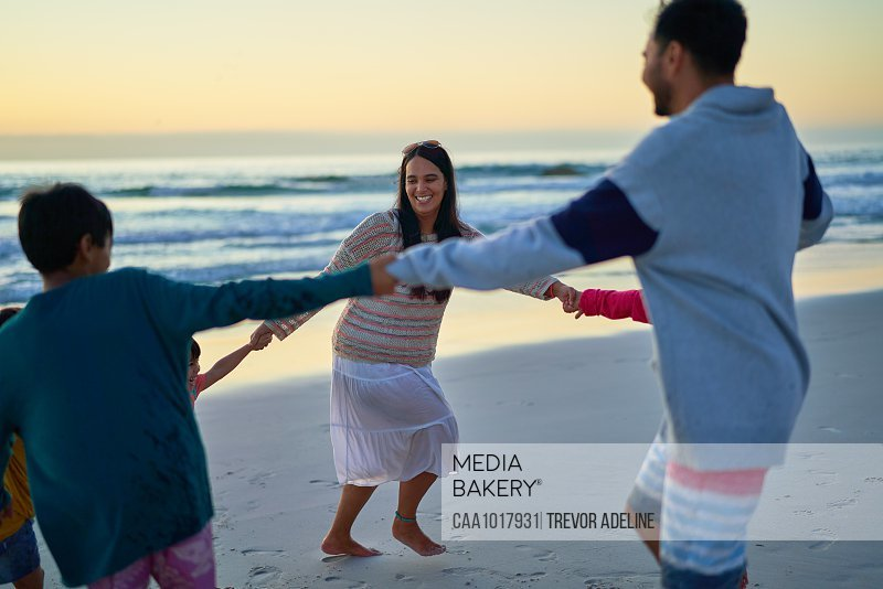 Happy family holding hands in circle on beach