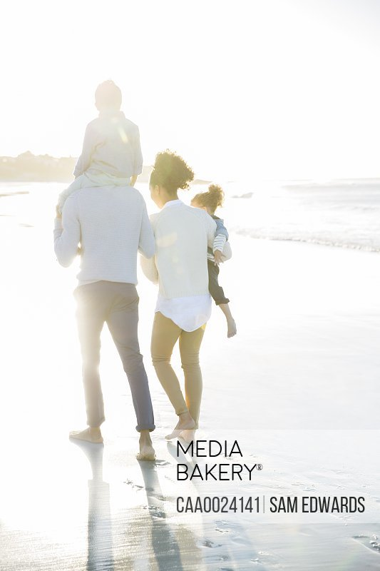 Family walking on beach in sunlight