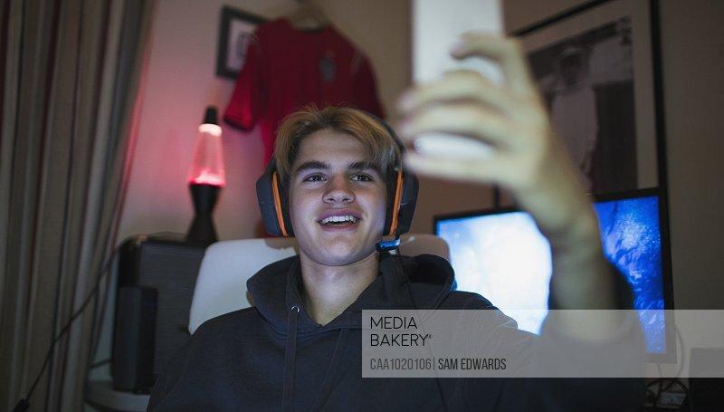 Smiling teenage boy with headphones taking selfie with smart phone