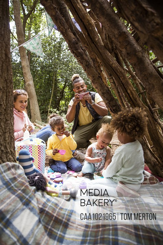 Family playing tea party in tree fort