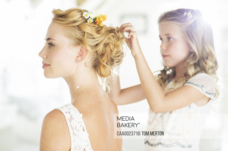 Bridesmaid helping bride with hairstyle in domestic room