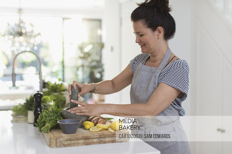 Woman cooking with mortar and pestle at cutting board in kitchen