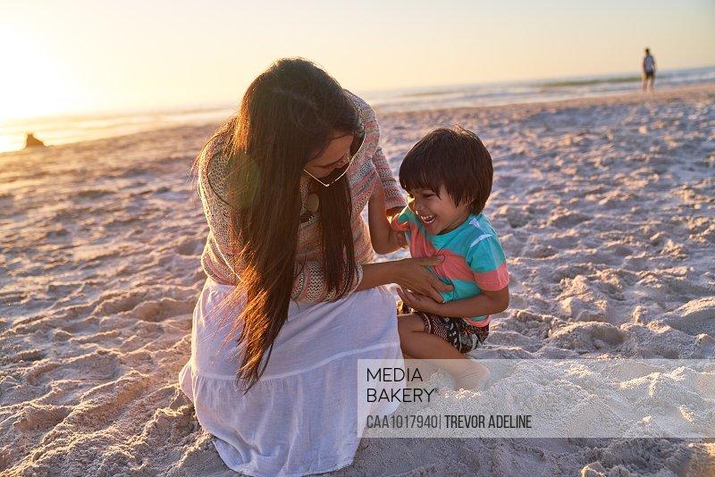 Playful mother tickling son on sunset beach