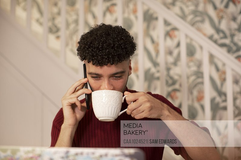 Young man with coffee talking on smart phone working at laptop