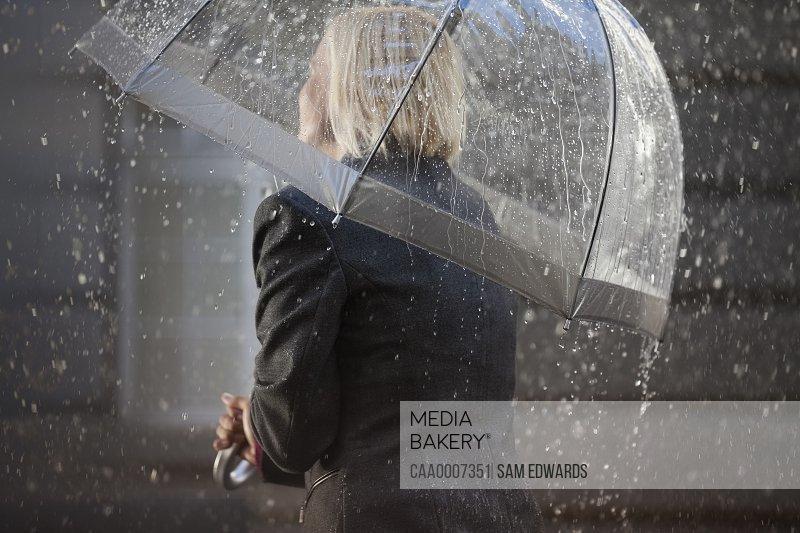 Businesswoman under umbrella in rain
