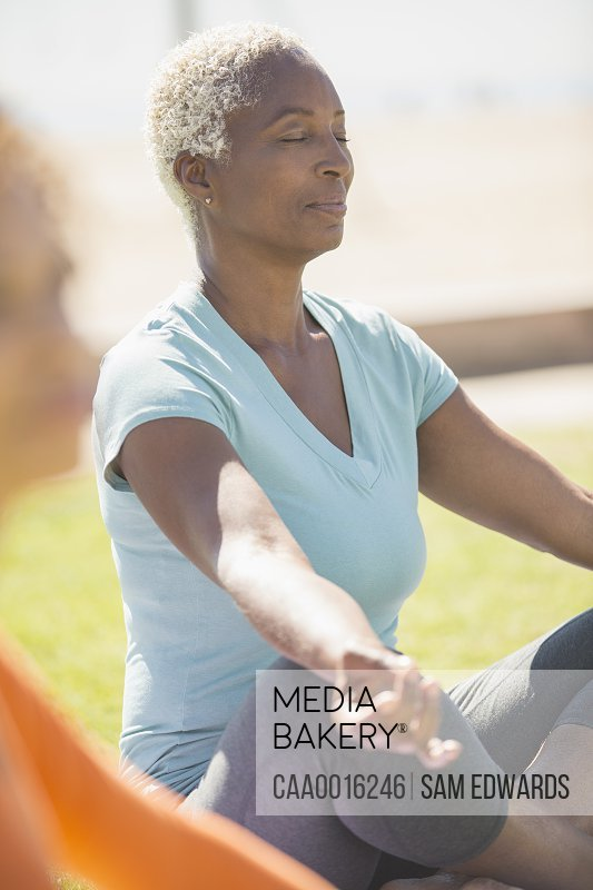 Serene woman meditating in lotus position outdoors
