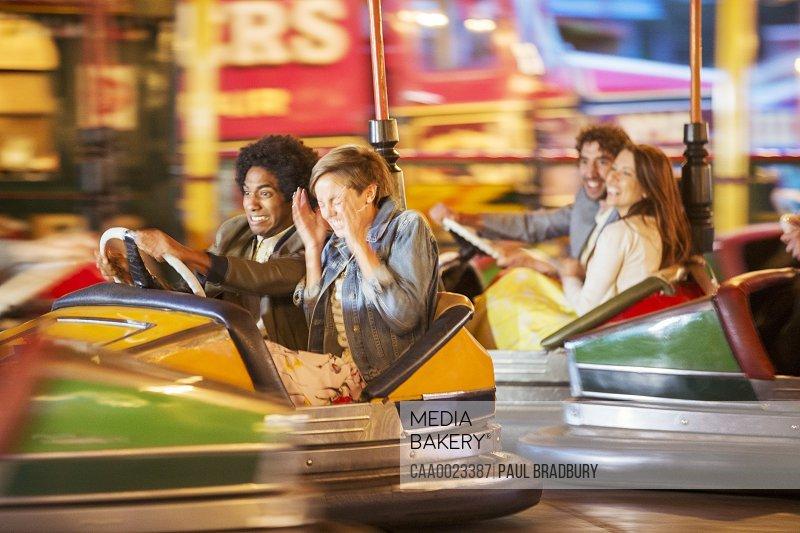 Group of friends having fun on bumper car ride in amusement park